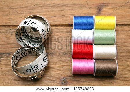 Multi-colored Cotton Reels And Tape Measure On A Wooden Sewing Table