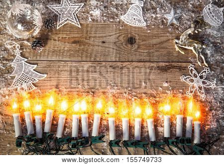 Christmas holiday candles background top view. Candle garland for greeting card. White snow old wooden board rustic style. Copyspace under fire