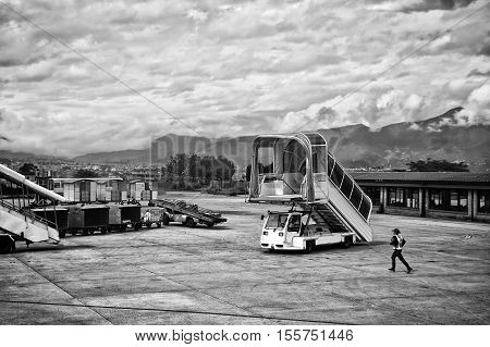 Kathmandu Nepal - July 23 2011: Airplane ladder on runway waiting for an aircraft (black and white). Cloudy sky. Tribhuvan International Airport is the sole international airport in Nepal