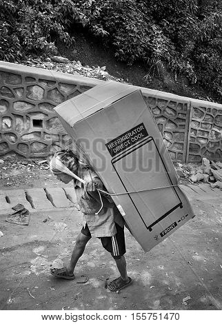 Kathmandu, Nepal - July 25, 2011: Nepali porter carrying refrigerator. Unskilled laborers are left behind in Nepal's economic