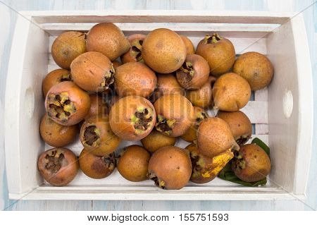 Medlar Fruit In A Wooden Box