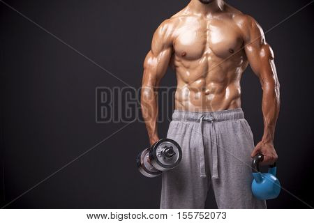 Cropped image of a bodybuilder holding a kettlebell and a dumbell against black background