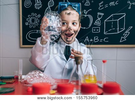 Portrait of excited little boy scientist with dirty face holding glass with soap foam against of blackboard with drawings
