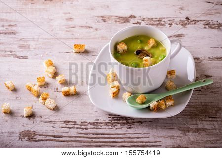 Split Pea Soup In Small White Cup On White Wooden Board