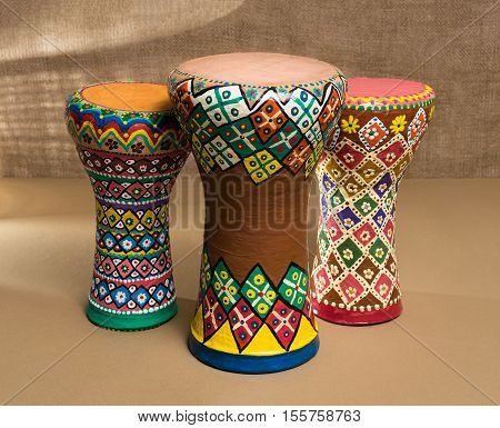 Front view of three decorated colorful pottery goblet drums (chalice drum tarabuka darbuka) on background of wooden table and sackcloth wall with grid shadows. Low light studio shot