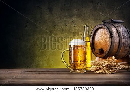 Faceted glass of beer, bottle and barrel on yellow background