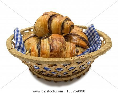 Fresh chocolate croissants in a straw basket with napkin isolated on white background.
