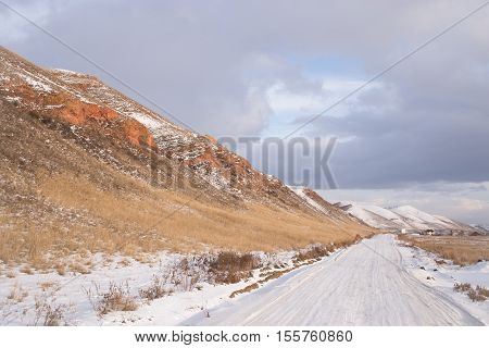 Winter rural road along the hill .