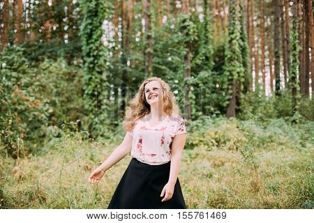 Young Pretty Plus Size Caucasian Happy Smiling Laughing Girl Woman With Wavy Brown Long Hair In White T-Shirt, Waltz Round In Summer Green Forest.