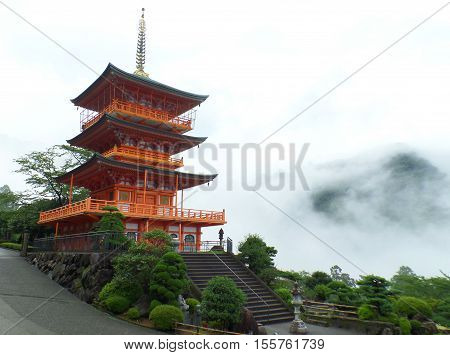 Stunning Bright Red Color Three-storied Pagoda in the Mist, Mountainside of Japan