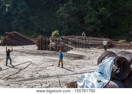 Bhulbhule, Nepal - October 23, 2014: Workers with steel rods at the construction site of the Upper Marsyangdi Hydropower Project in the Annapurna Region