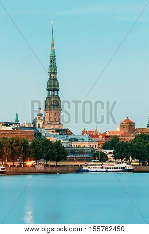 Latvia, Riga The View Of St. Peter's Church Tower Behind Daugava River Quay, Old Town In Summer Dusk Under Blue Sky.