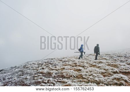Two Tourist Photographer With Tripod On Hand Walking On Frozen Hill With Fog.