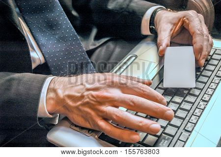 Businessman holding blank business card with laptop on background