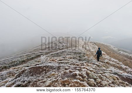 Tourist Photographer With Tripod On Hand Walking On Frozen Hill With Fog.