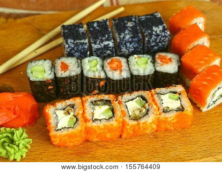 japanese sushi roll set in row on wooden kitchen board with sticks vasabi mustard and ginger close up photo