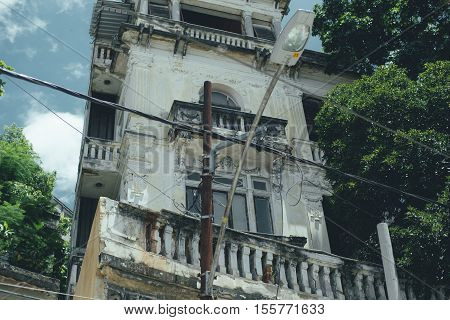 View of facade of old moldy house with dilapidated balconies and lantern with wires in front Rio de Janeiro Brazil