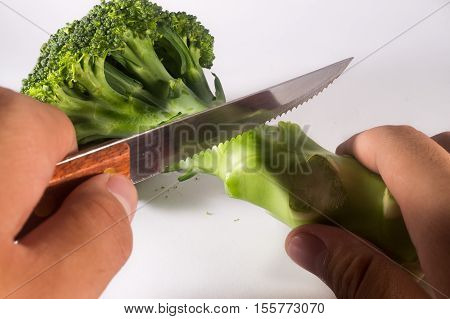 Brocolli Cut With Knife Holded By Person On White Background