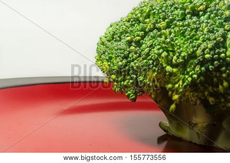 Green Brocolli On Red And Black Plate On White Background