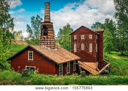 Old ironworks, a red wooden building. standing in a lush green environment. poster
