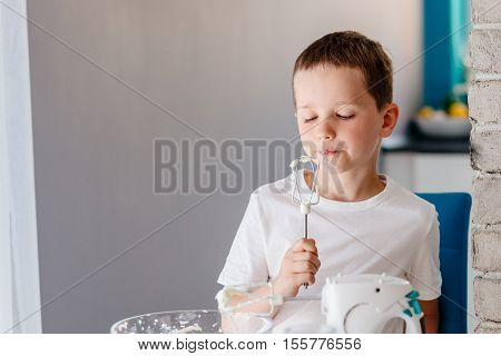 Child Tasting Pastry From Mixer Agitator