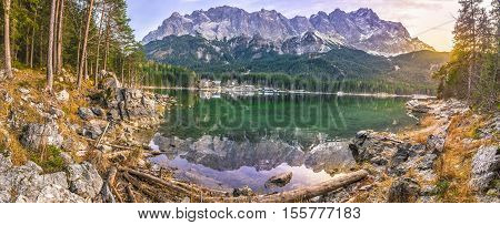 Alpine panorama with the German Alps mountains reflected in the Eibsee lake and green coniferous forest at sunset in December.