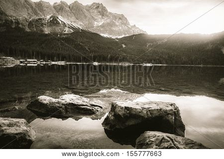 Vintage picture with mountains and lake - Dreamy monochrome landscape with the clear water of the Eibsee lake and the German Alps mountains reflected in it on a sunny day of December.