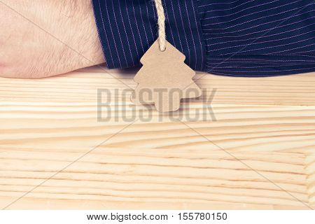 Pine tree shaped label tied with twine to an elegant man or businessman. Natural wooden table. Giving oneself as a present or gift abstract concept. Vintage colors.