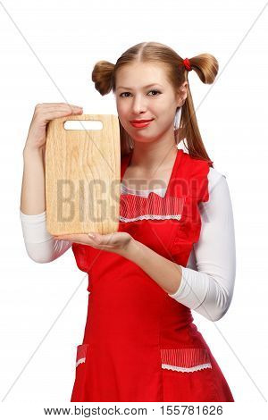 Young beautiful attractive smiling housewife in bright red apron with funny ponytails holding rectangular wooden cutting board isolated on white background.