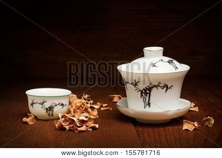 Porcelain Set For Chinese Tea Ceremony Of White Gaiwan And Cup Standing At Brown Wooden Table With D