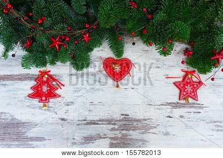 christmas fresh evergreen tree branches with red vintage heart, christas tree and star decorations on white aged wood