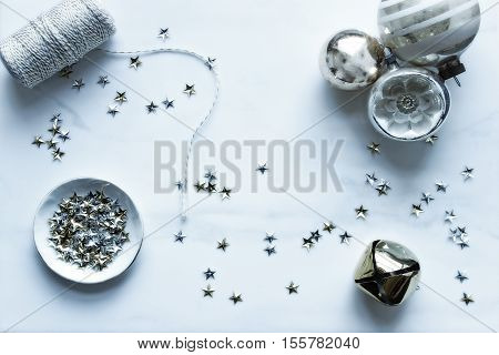 Over head flat lay view of Christmas winter desktop. White, gold and silver accents. Vintage ornaments, twine, stars and jingle bell. Open space for text