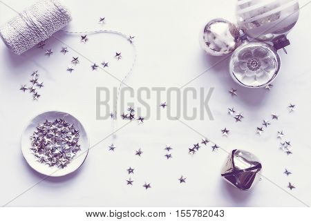 Over head flat lay view of Christmas winter desktop. White, gold and silver accents. Vintage ornaments, twine, stars and jingle bell. Open space for text.