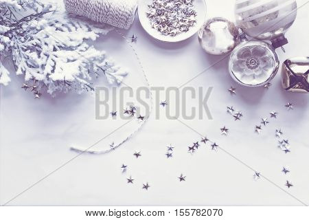 Christmas Winter Desktop with white, silver and gold accents. Vintage ornaments, stars, jingle bell, twine and pine branch.