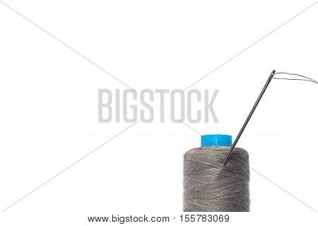 Spool of gray thread, sewing needle and thread. insulation.