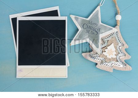Blue and white christmas with stras and instant photo on blue wooden background, vintage style