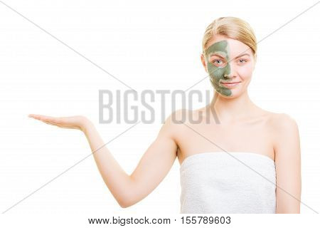 Skin care. Woman in clay mud mask on face holding open palm empty hand for product isolated. Girl taking care of dry complexion. Beauty treatment.