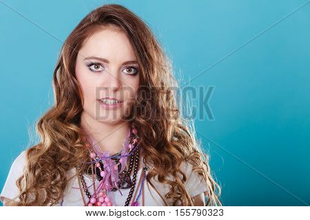 Pretty young woman wearing many plenty of jewelry necklaces beads. Portrait of gorgeous fashion girl in studio on blue.