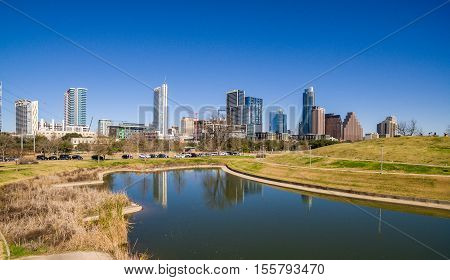 Austin Texas Skyline reflection from Butler Park Pond during a dry summer day with blue sky and Clear View of the Downtown cityscape