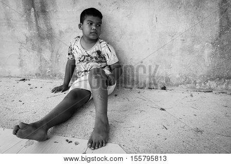 kid pauper sitting against the concrete wallblack and white tonefocus leg