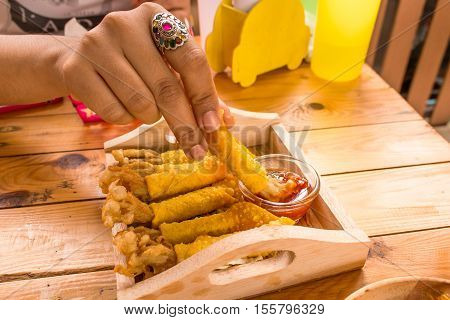 Golden needle mushroom with wonton fried on wooden dish