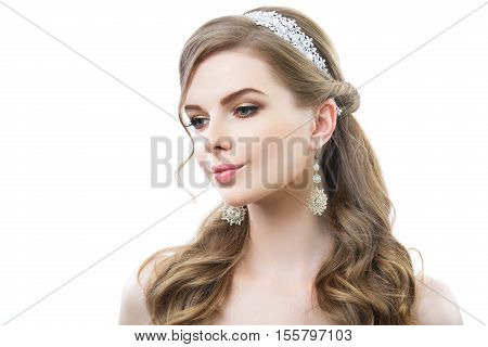 Beautiful woman with long curly hair. On her white earrings and headband. Pink lips and golden eyelids makeup.