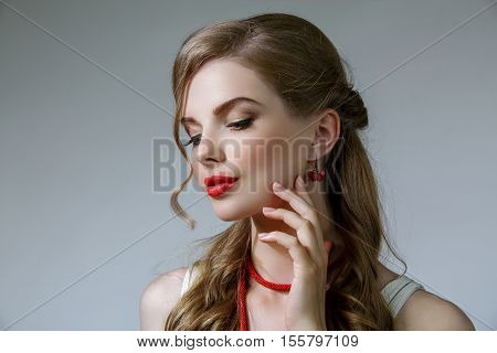 Beautiful woman with long wavy hair. She wear red earrings and beads on her neck. Red lips and golden eyelids makeup. Isolated on gray background.
