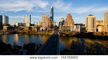 Austin Texas skyline cityscape with golden sunshine cast on the downtown cityscape skyscrapers Office buildings on a panoramic mirror image off the calm waters of Town Lake