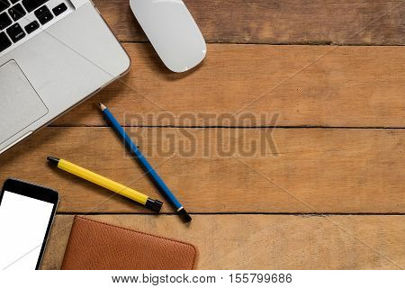 Office desk table with laptop mouse pen pencil blank screen smartphone and leather notebook.Top view with copy space.Office supplies and gadgets concept.