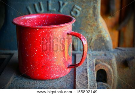 An image of a red tin coffee cup on an old metal bench.