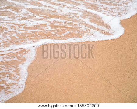 Sea wave to the beautiful sand leaving copyspace at bottom left able to use as background