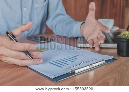 Business man discussing the analysis charts or graphs on desk table.Business concept.Vintage tone.