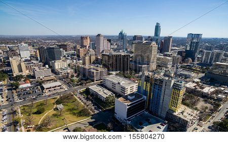 Aerial Over Austin Texas Skyline Cityscape Mid Day Full Sun Blue Sky high above new construction and Skyscrapers with Frost Bank Tower background