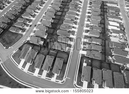 Black and white Houses aerial over Community Suburbia new development modern homes outside of Austin Texas rows and rows of the same houses